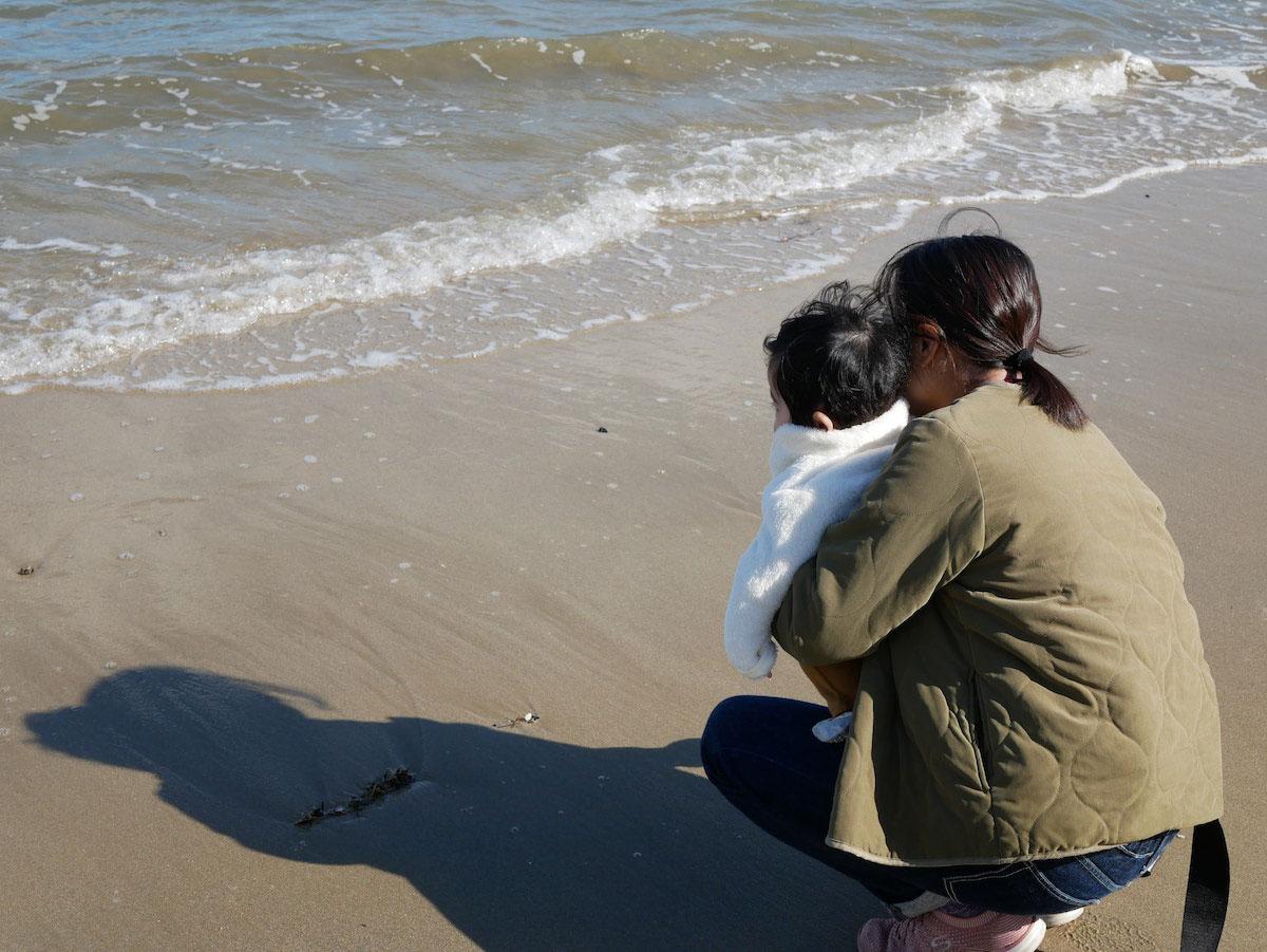 子供と一緒に海を見ている様子