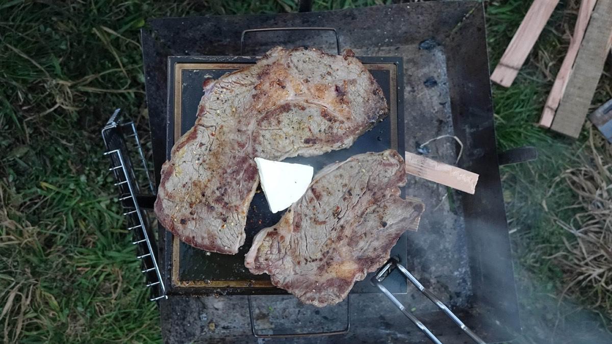 キャンプ用の鉄板でステーキ肉を焼く