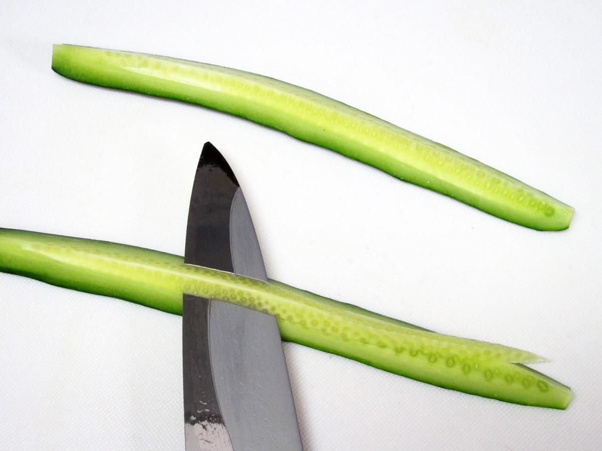 きゅうりを縦に半分に切り、種の部分をそぎ落とします
