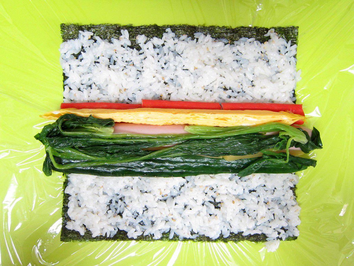 海苔の中央部に玉子焼き、ほうれん草ナムル、にんじんナムル、きゅうり、魚肉ソーセージ、たくあん、カニカマのそれぞれ半量をのせます
