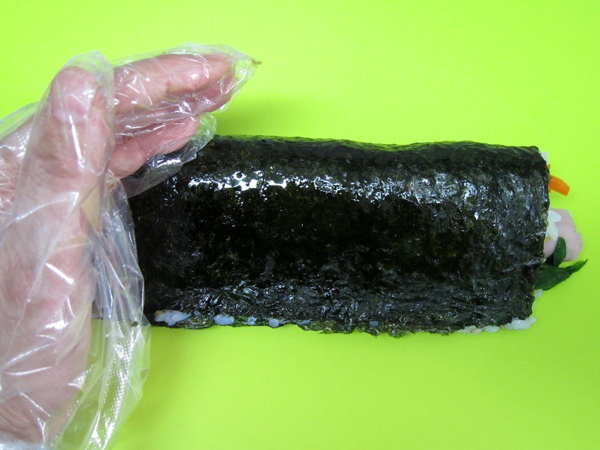 巻き終えたらラップの上から形を整えたらラップをはずし、ゴマ油を海苔にまぶします