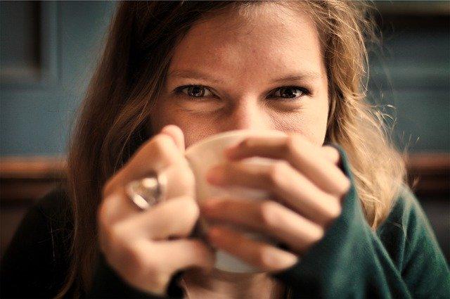 マグカップを口元にあてて幸せにほほ笑む女性