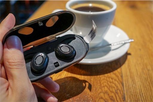 充電ケースに収納された状態でのコーヒーとの大きさ比較をしているところ