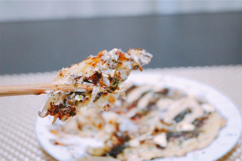 海鮮お好み焼きを箸で摘む写真
