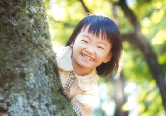 木に隠れた笑顔の子供の画像