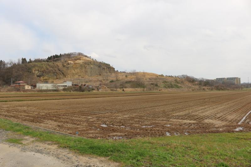 土石を採取している山が岩倉館跡(写真右の建物は秋田県立大学)