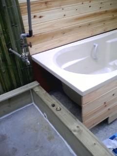 寝湯の枠の中にコンクリートを流し、バスタブをフローリング材で囲う。