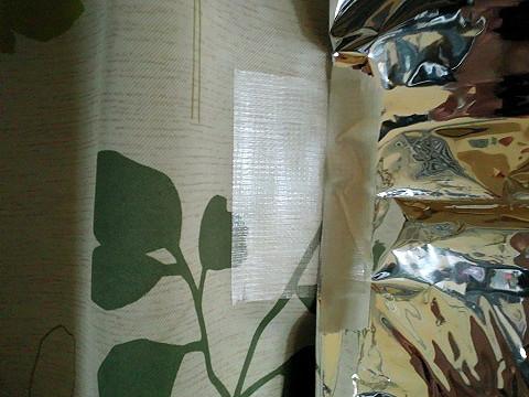 アルミシートを養生テープでカーテンに貼る