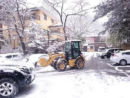 除雪中の宿スタッフ