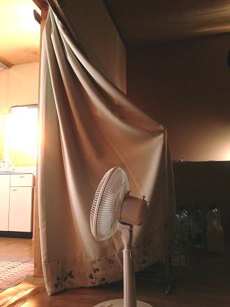 マガジンラックで広げたカーテンと扇風機