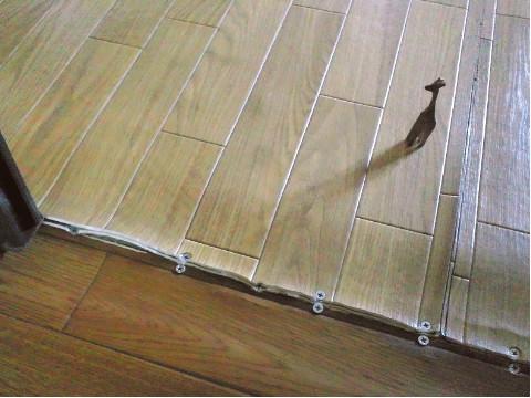 両面テープと木ネジで押さえたクッションフロアの継ぎ目