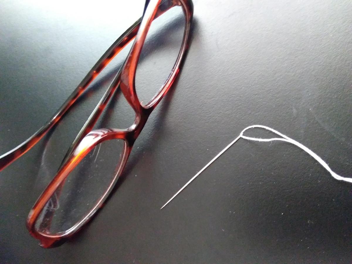 老眼鏡、白い糸を通した縫い針
