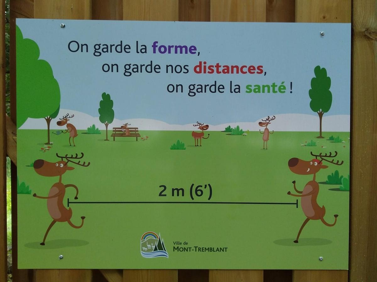 自転車道沿道のポスター、コロナ対策の2メーターの距離を確保することを訴える内容、コミカルな鹿のデザイン