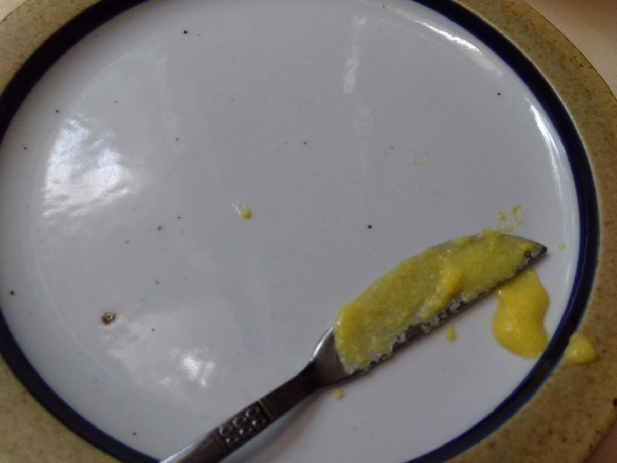 空の皿とコーンバターがついたバターナイフ