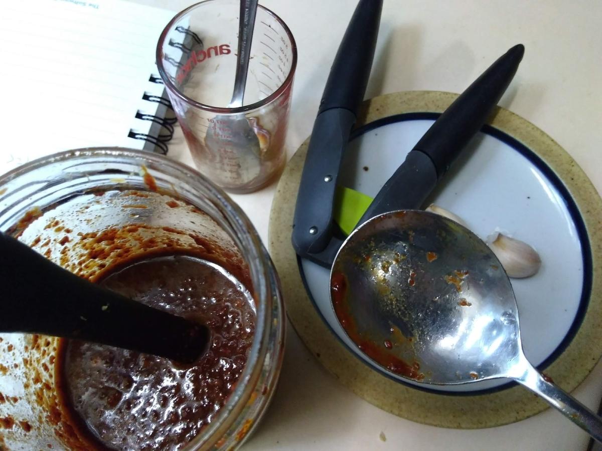 チゲの味付けよう調味料を入れたガラス瓶と計量カップ、ニンニク、大匙