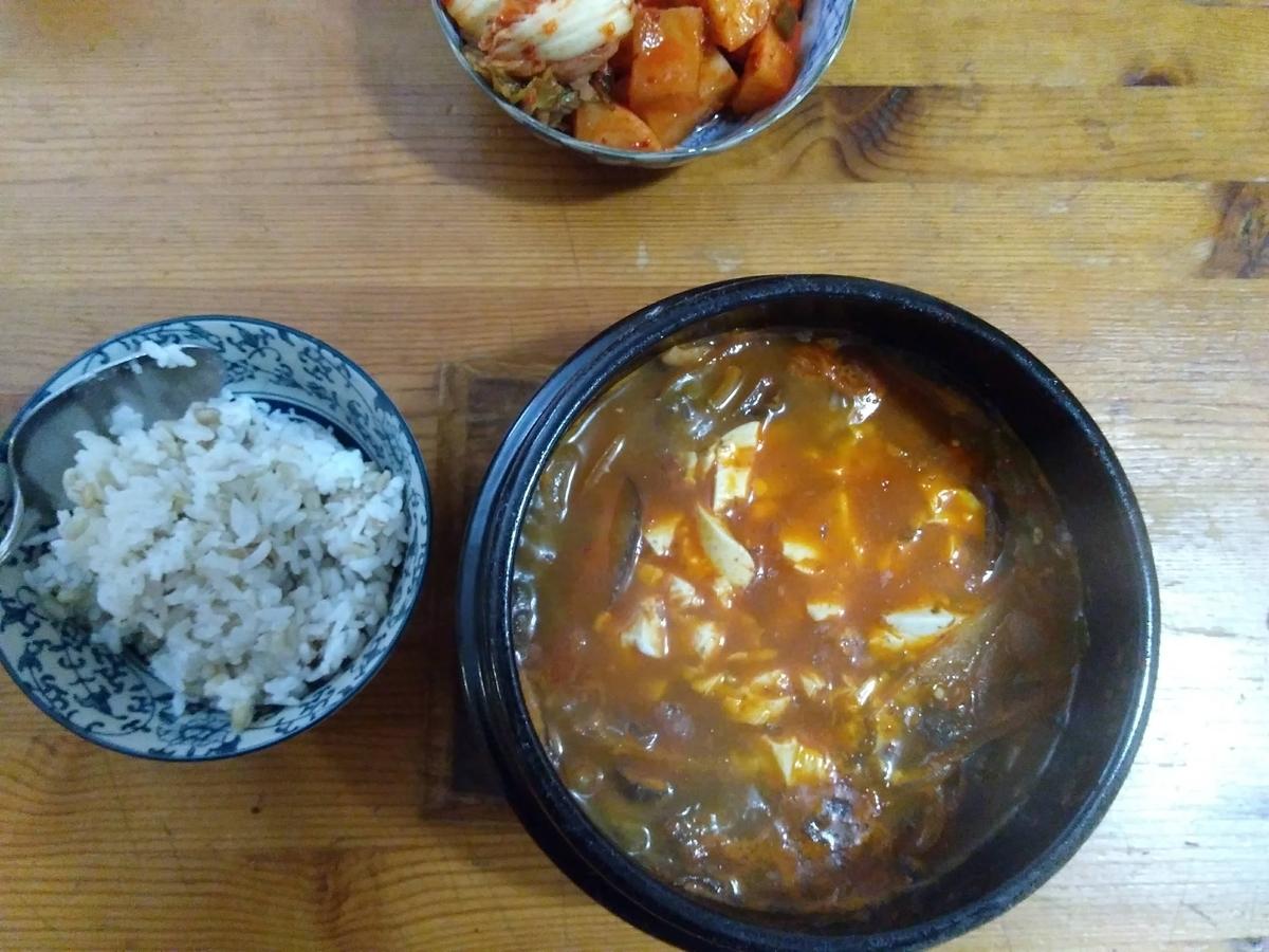 ヴィーガン純豆腐チゲ、麦入白米、キムチ、食卓に乗っている図