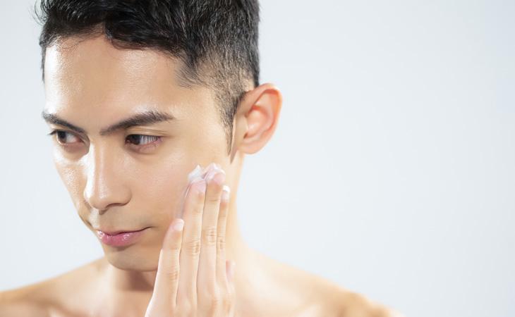洗顔後にジェルを顔に塗る男性。