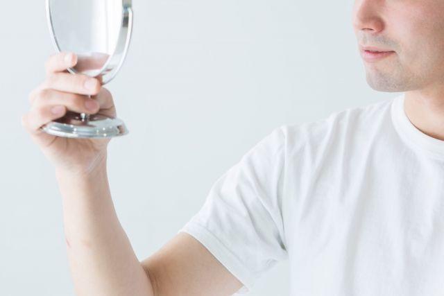 手鏡で自分の肌の状態をチェックする男性