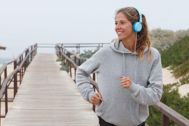 ヘッドホンで音楽を聴きながらランニングする女性