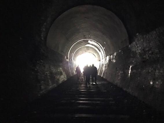 トンネルを歩く犬と人
