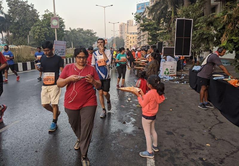 ムンバイマラソンでオレンジを配る少女