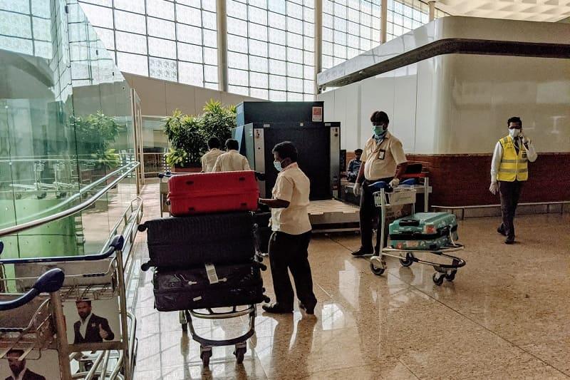 預入荷物を手作業で運ぶ空港職員