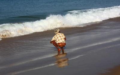 海辺でしゃがみ込む男性