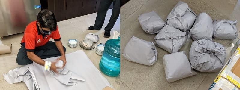 食器を緩衝材で包む作業員