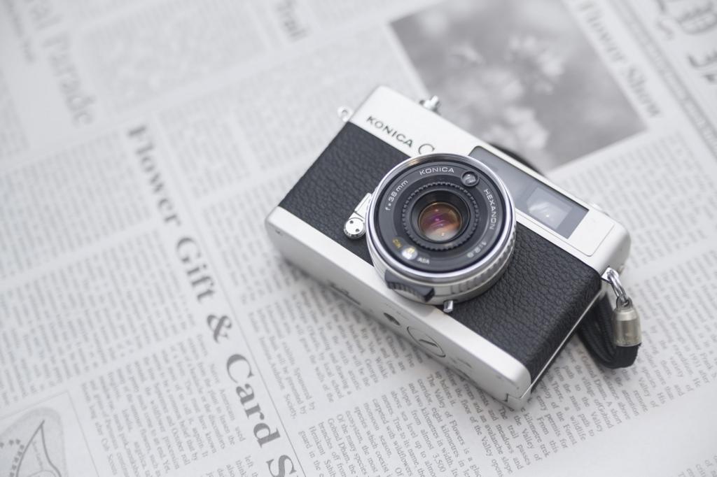 カメラと英字新聞の写真