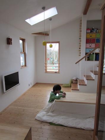 天井が高いおかげで広く感じるリビングでくつろぐ子ども