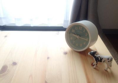 テーブルの上に牛のフィギュアと時計があるところ