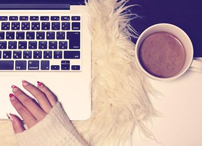 ノートパソコンとコーヒーと手