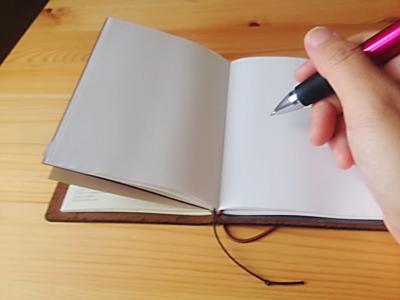 トラベラーズノートに書いているところ