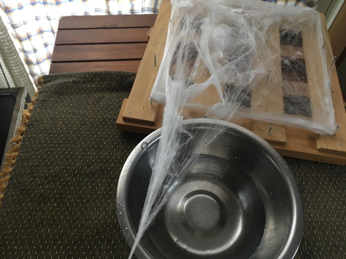 すのこの器具から真綿をひっぱって糸にする様子