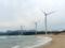 砂浜に並ぶ風力発電のプロペラ