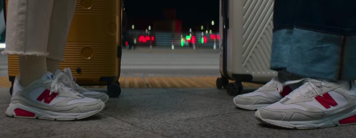 ペアルックの赤いNBロゴの靴を履くダウンとヒョク