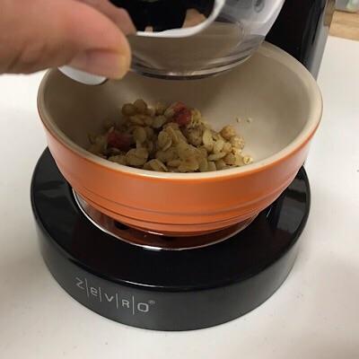 フードディスペンサーを使用してお皿にフルグラを入れるところ