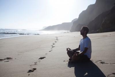 浜辺で瞑想する男性