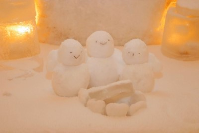 淡いライトに照らされた3つの小さい雪だるま