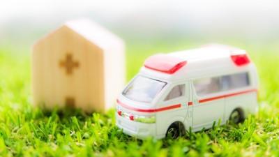 木製のお家のミニチュアと救急車のミニカー