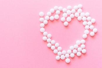 ピンクの背景に白い錠剤で作ったハート