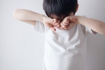 白いシャツを着た両手を顔に当てて泣いている男の子