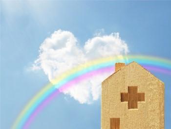 木製の病院のミニチュアとハートの雲と虹