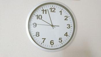 白い壁にかかった銀色の枠の掛け時計