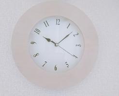 白い壁にかかった淡い白の木枠の掛け時計