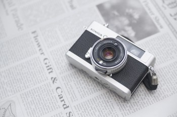 英字新聞の上に置かれたカメラ
