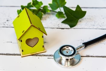 黄緑色の木製のお家のミニチュアと聴診器