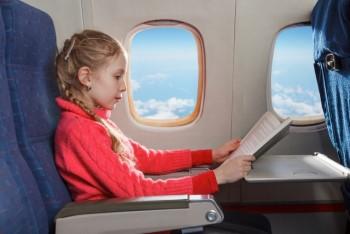 飛行機の中で本を読む女の子