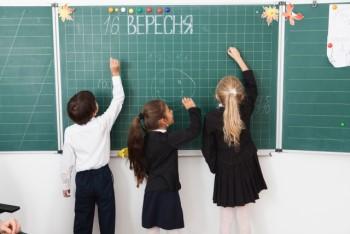 黒板に向かって書こうとしている小学生3人