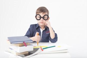 積み重ねた本の山と黒い大きな眼鏡をかけた男の子